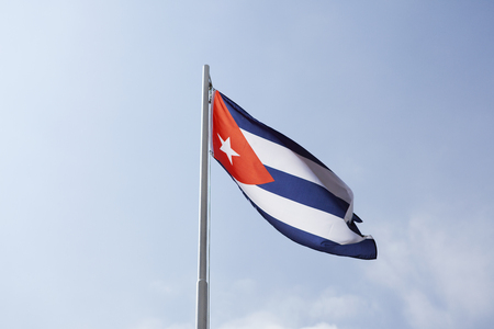 middle america: National flag of Cuba on a flagpole in front of blue sky