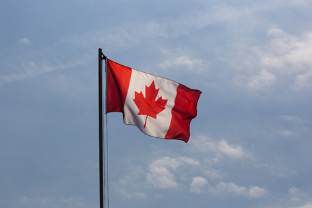 flagpole: National flag of Canada on a flagpole in front of blue sky Stock Photo
