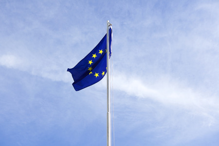 flagpole: Flag of European Union on a flagpole in front of blue sky
