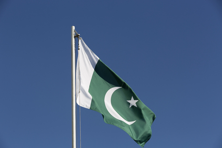 National flag of Pakistan on a flagpole in front of blue sky