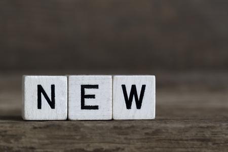 unworn: New, written in cubes on wooden background Stock Photo