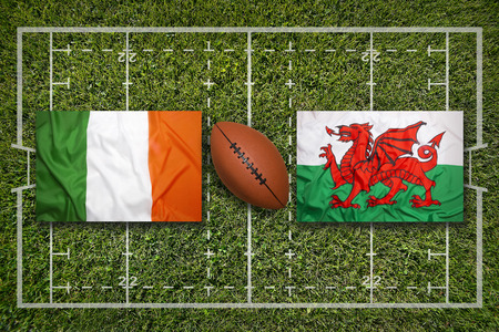 wales: Ireland vs. Wales flags on green rugby field Stock Photo