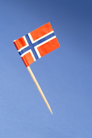 Paper flag of Norway on blue background
