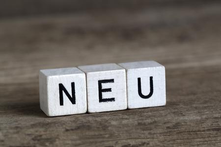 unworn: German word new, written in cubes on a wooden background