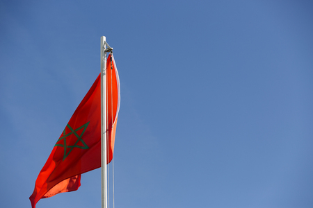 National flag of Morocco on a flagpole in front of blue sky Standard-Bild