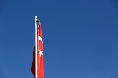 National flag of Turkey on a flagpole in front of blue sky