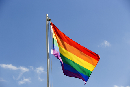 Rainbow flag on a flagpole in front of blue sky