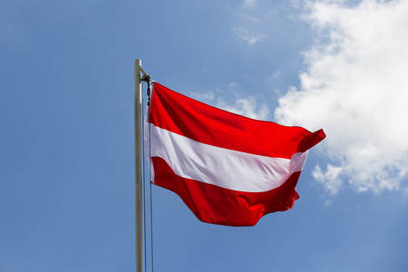 National flag of Austria on a flagpole in front of blue sky
