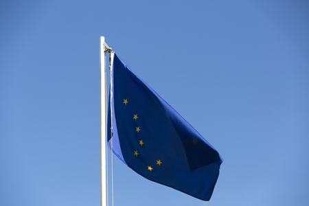 National flag of Alaska on a flagpole in front of blue sky