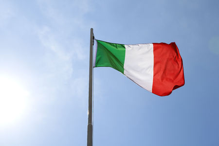 National flag of Italy on a flagpole in front of blue sky Standard-Bild