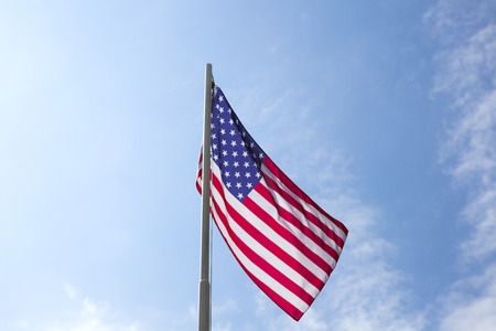 Flag of United States on a flagpole in front of blue sky Standard-Bild