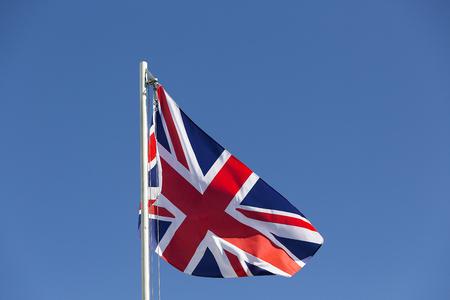 UK flag on a flagpole in front of blue sky Standard-Bild