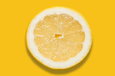 Piece of lemon on colorful yellow background