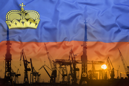Industrial concept with Liechtenstein flag at sunset, silhouette of container harbor
