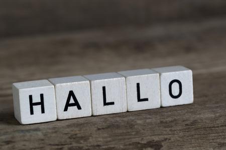 Duits woord hallo, geschreven in blokjes op een houten achtergrond Stockfoto