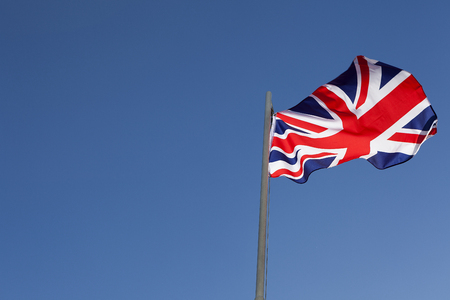 UK flag on a flagpole in front of blue sky Stock Photo
