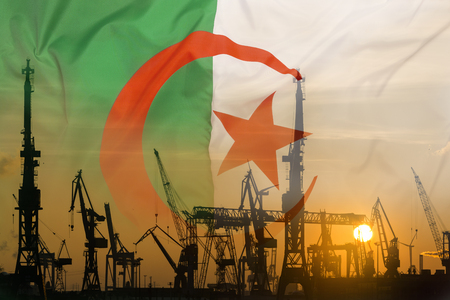 Industrial concept with Algeria flag at sunset, silhouette of container harbor