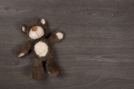 Brown teddy bear on a wooden background, top view Archivio Fotografico