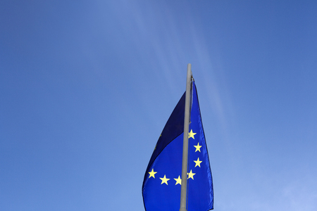 Flag of European Union on a flagpole in front of blue sky