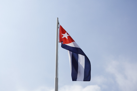 National flag of Cuba on a flagpole in front of blue sky