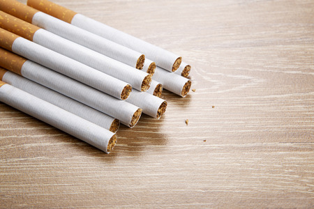 Several cigarettes on a wooden background