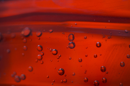 Different bubbles in a red oil liquid, close-up