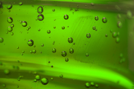 Different bubbles in a green oil liquid, close-up