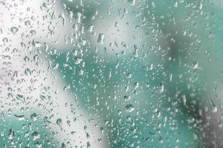 Raindrops on a windowpane with blue background