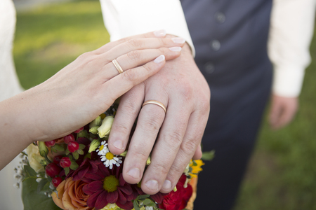 Hands of bride and groom with flower bouquet and wedding rings