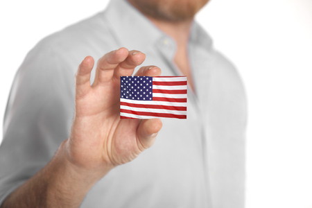 Caucasian businessman in blue shirt holding business card with USA flag