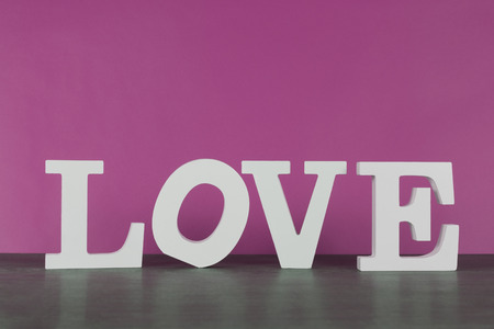 The word love written in white letters in front of pink background, home living