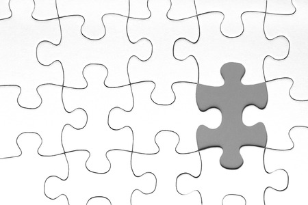 Gray puzzle piece in between of white puzzle pieces, business concept