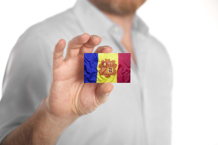 Caucasian businessman in blue shirt holding business card with Andorra flag
