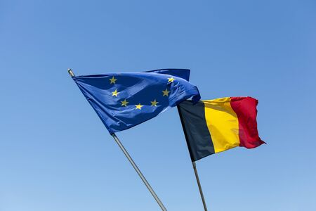 European flag with Belgium flag in front of blue sky