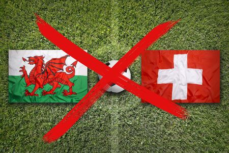 Canceled soccer game, Wales vs. Switzerland flags on green soccer field