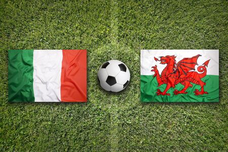 Italy vs. Wales flags on green soccer field