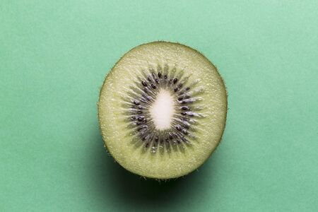 Kiwi fruit in front of a green background