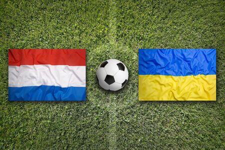 Netherlands vs. Ukraine flags on a green soccer field