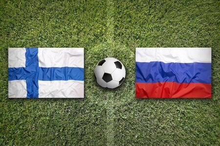 Finland vs. Russia flags on green soccer field 写真素材