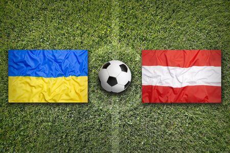 Ukraine vs. Austria flags on green soccer field
