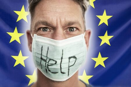 Portrait of a caucasian man in medical mask in front of Europe flag. Coronavirus concept, respiratory protection