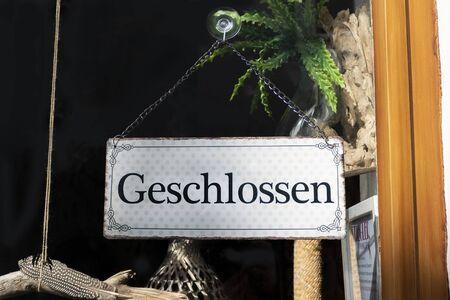 Closed sign in a shop door, german