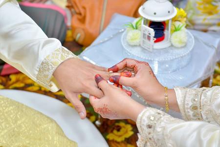 Bride puts on wedding ring on grooms finger