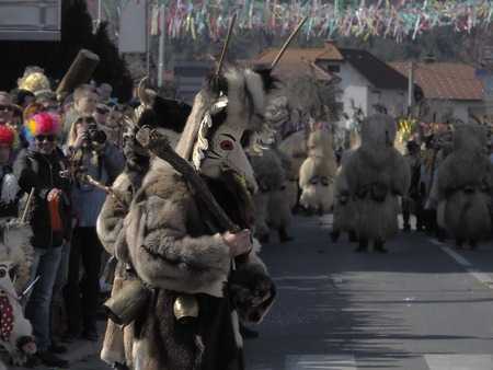 People wearing Kurent costumes walk down the street during parade in Slovenia with crowd watching in the background.