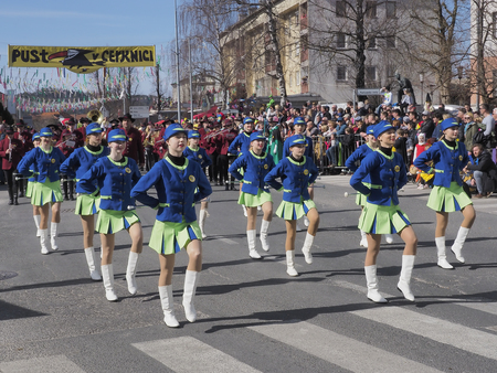 Group of young females baton twirlers preform for the crowd in front of a marching band in an annual spring time carnival parade in Slovenia.
