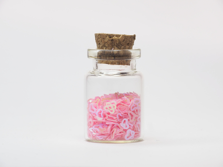 Isolated profile of tiny pink plastic hearts are in a small glass bottle with a cork stopper.