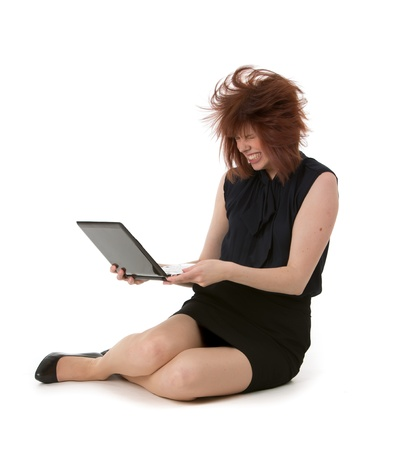 temper: Woman throwing a temper tantrum gnashing her teeth and shaking her laptop computer while sitting on the floor with her hair in disarray, on white