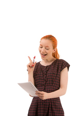 emphasise: Pretty young redhead woman busy giving a presentation reading from a notebook and raising her finger to emphasise a point, isolated on white