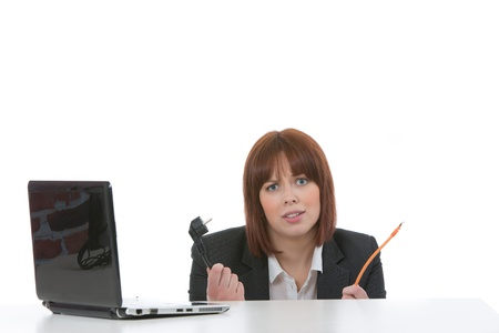 ignorant: Ignorant woman peering over the top of a table with a laptop on it holding computer cables in her hands with a look of confusion, on white