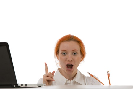 mouthed: Woman making a breakthrough and suddenly understanding the solution raising her finger in open mouthed surprise as she holds the cables for her laptop in her hand